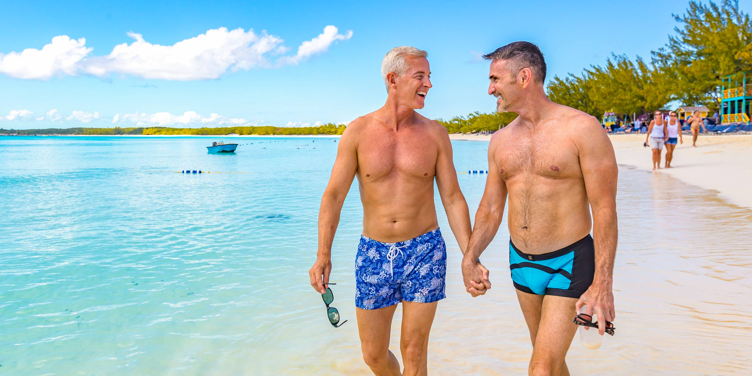 Two men holdings hands while looking at each other and smiling while walking down the beach
