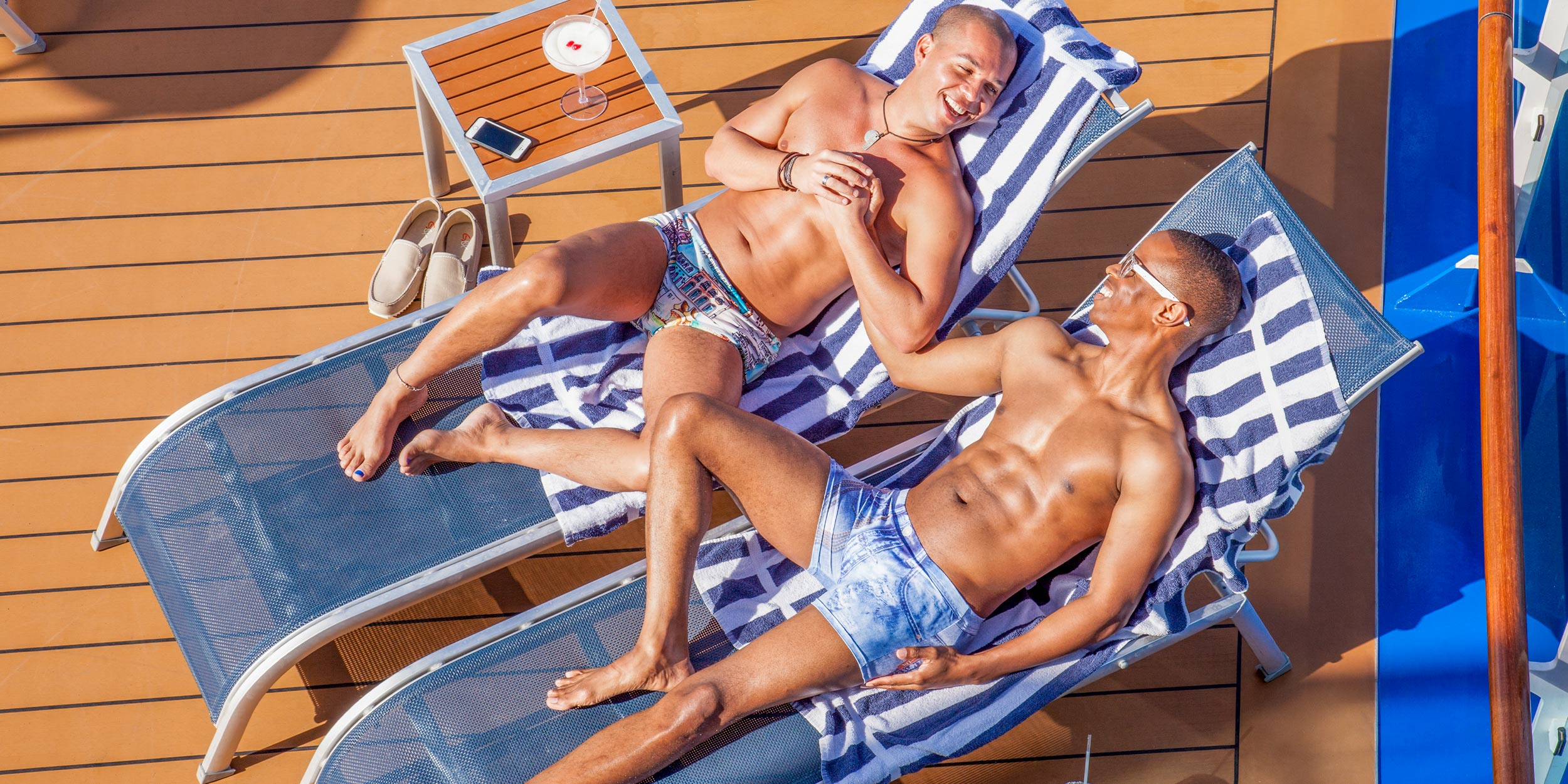 Two men laying down shirtless on lawn chairs on a sunny pool deck smiling and laughing at each other