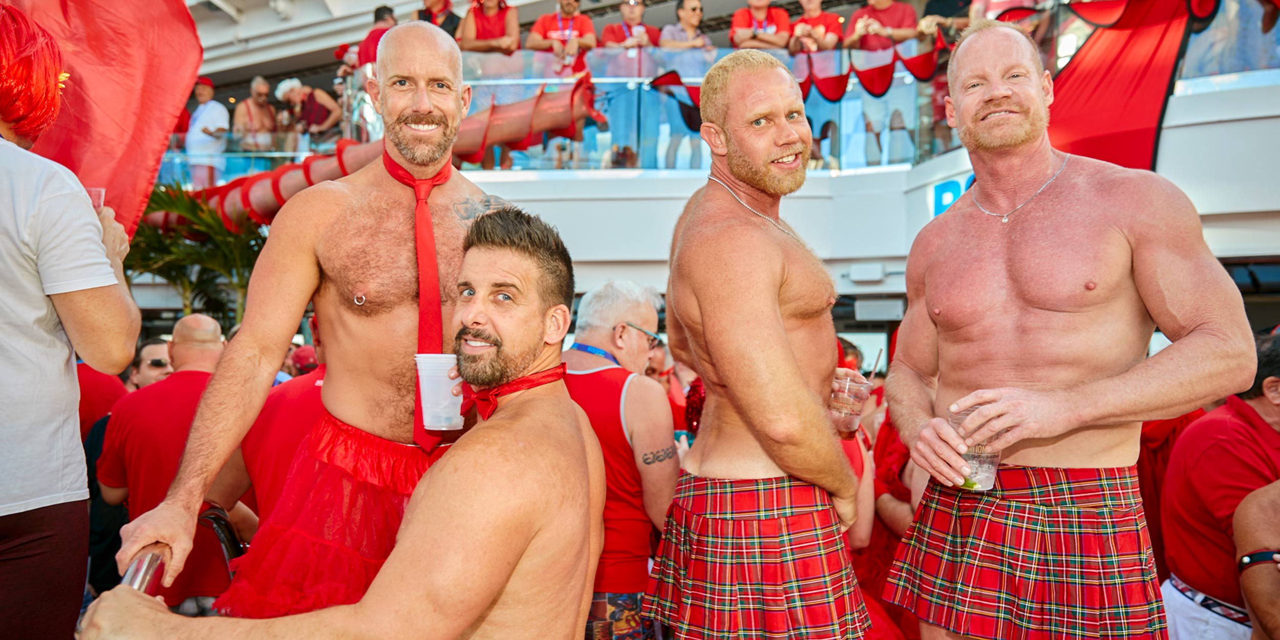 Four shirtless men dancing at a party dressed in red